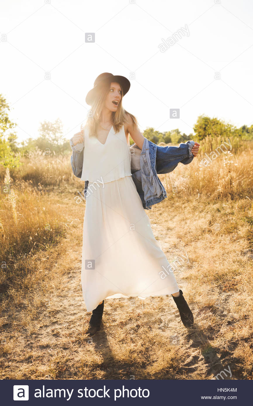 Belle blonde femme dans une longue robe blanche, veste en jean et hat  posing sur 5811bf65fa8