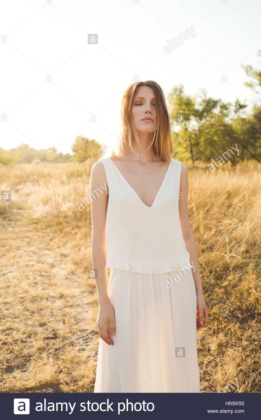 Belle blonde femme dans une longue robe blanche posant dans le domaine.  Style Boho Photo 178cd797878