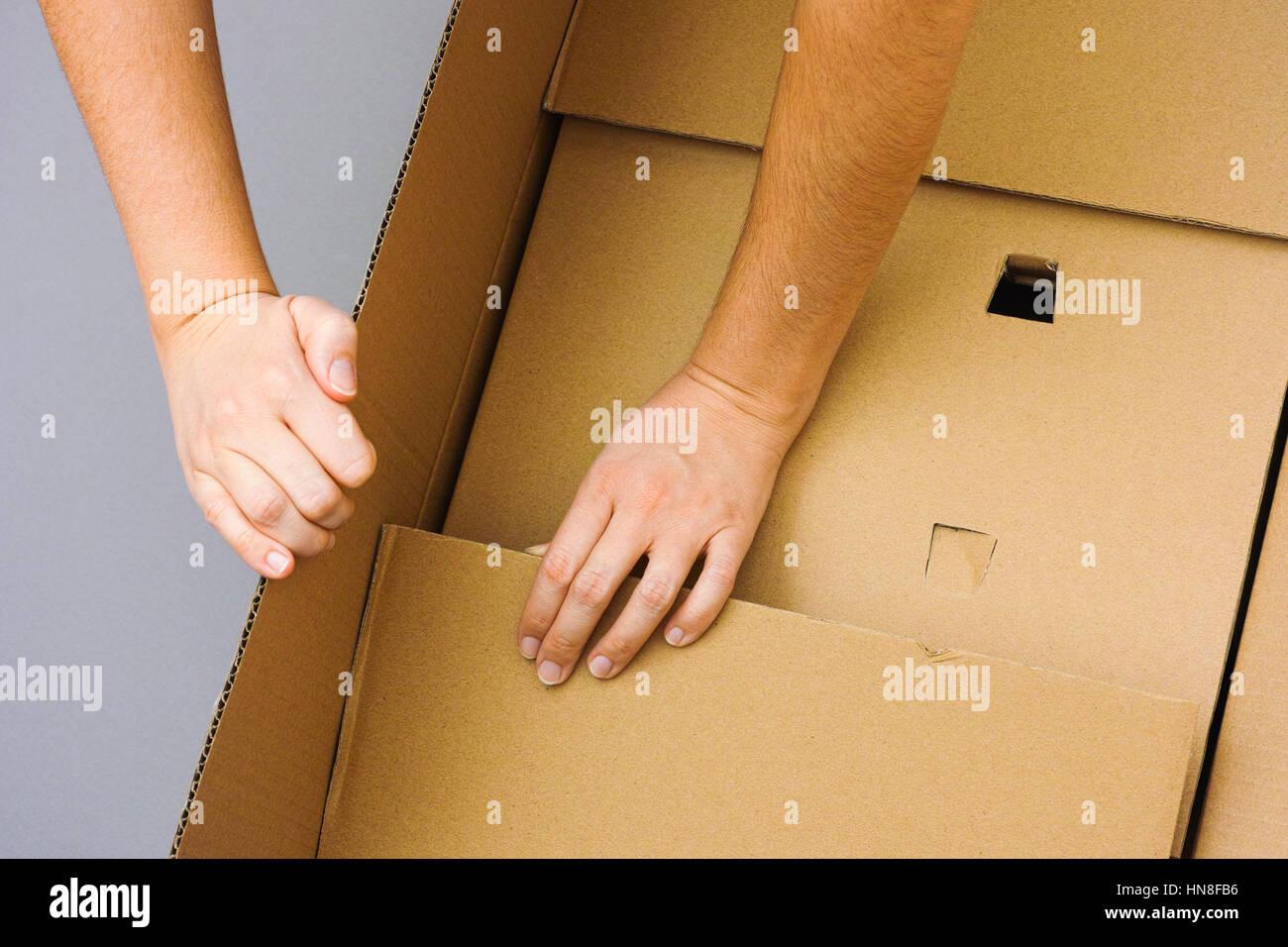 Deux mains femme grande ouverture du carton. Fond gris. Photo Stock