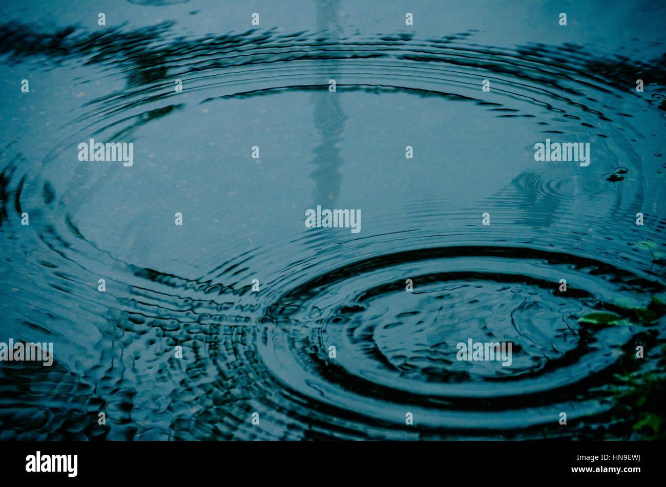 Forme de gouttes de cercles sur les flaques d'eau ou on city street. Photo Stock