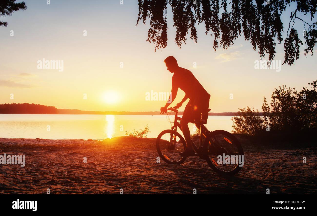 Garçon sur un vélo au coucher du soleil Photo Stock