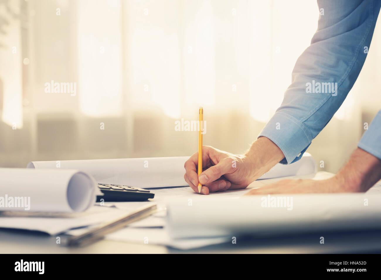Travailler avec l'architecte blueprints in office Photo Stock