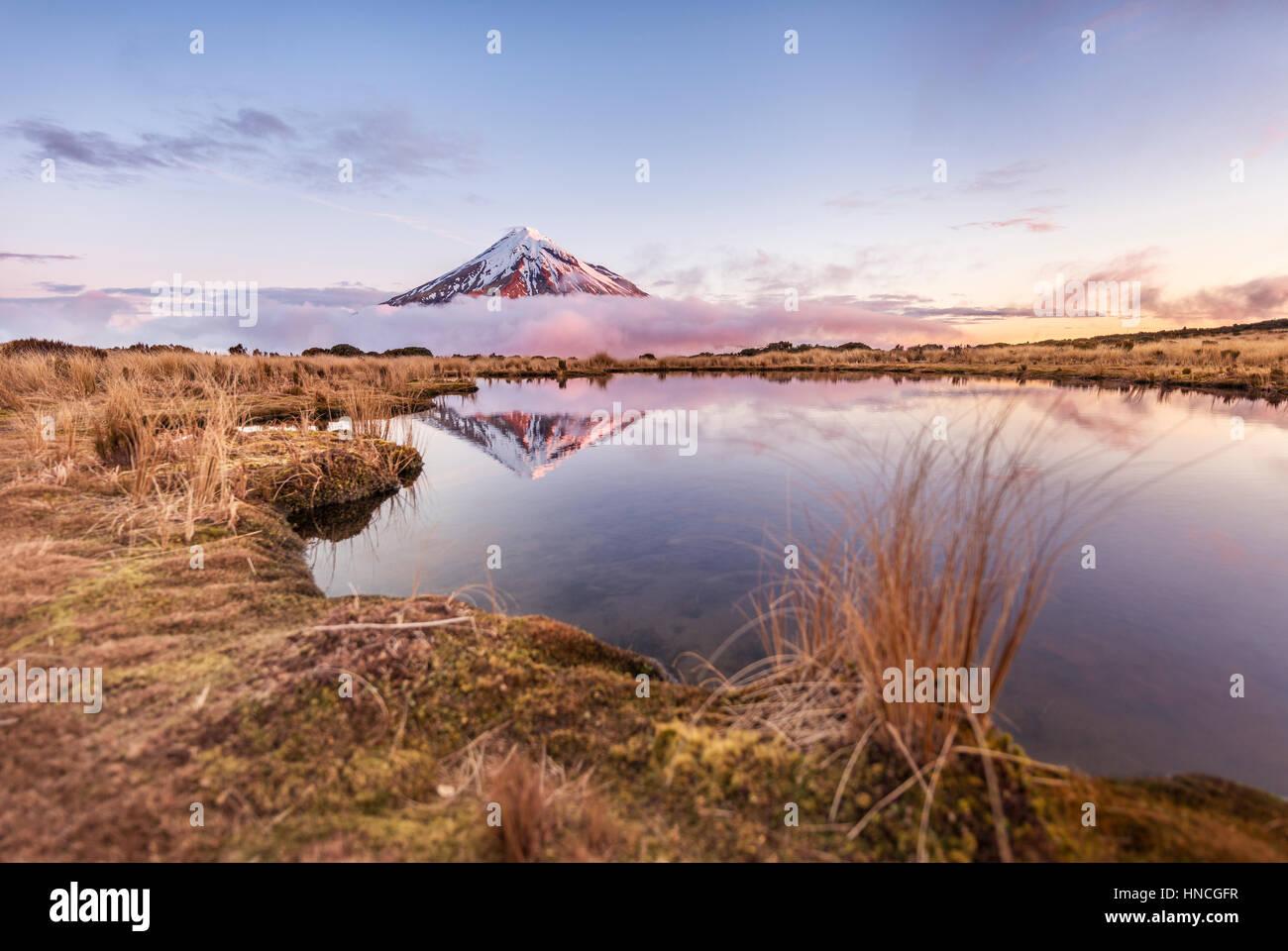 Reflet dans le lac rose Pouakai Tarn, nuages autour du Mont Taranaki ou Mont stratovolcan Egmont au coucher du soleil, Photo Stock