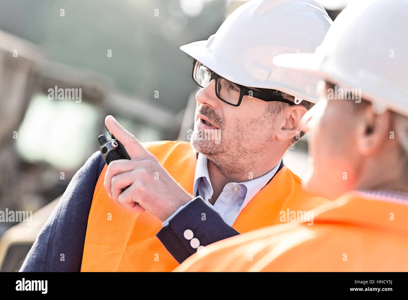 Superviseur montrant quelque chose à collègue at construction site Photo Stock