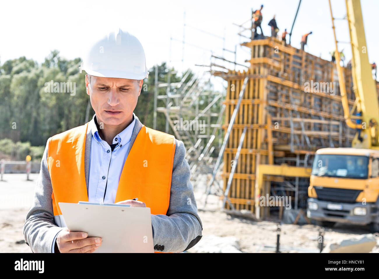 Supervisor writing on clipboard at construction site Banque D'Images
