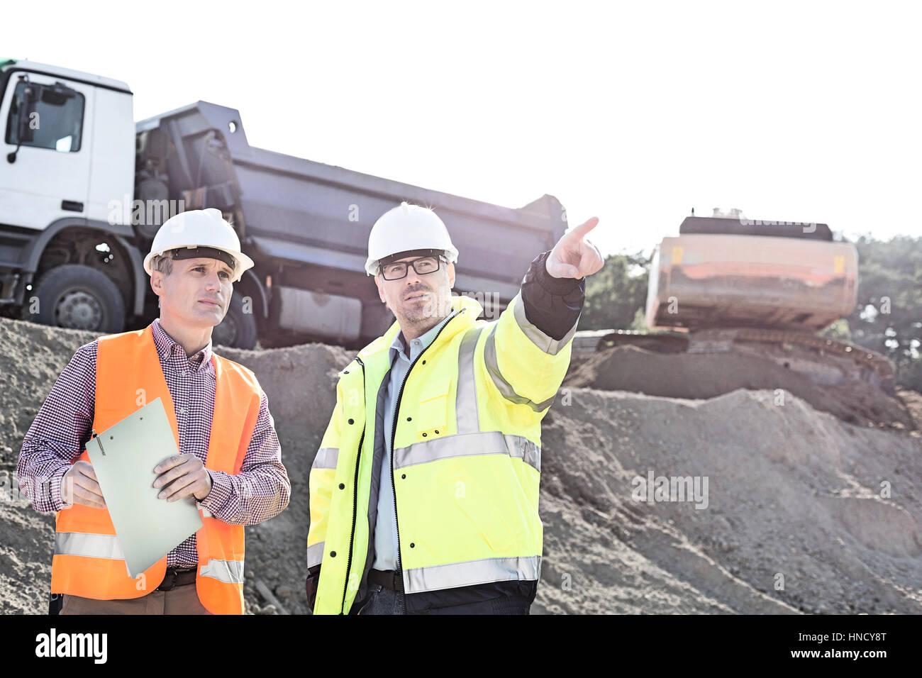 Superviseur montrant quelque chose à tes collègues tout en discutant at construction site Photo Stock