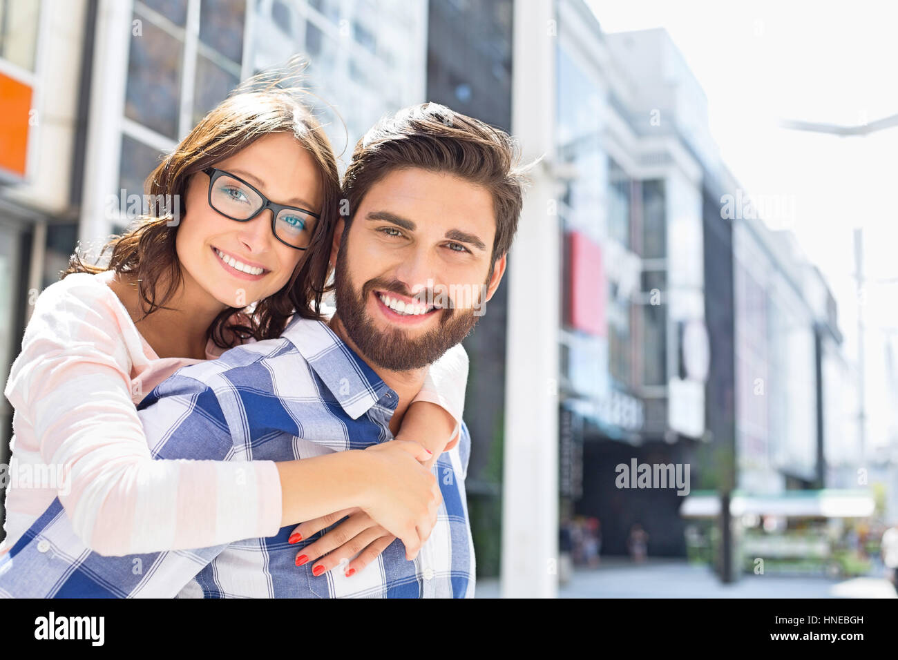 Portrait of happy man giving piggyback ride to woman in city Photo Stock
