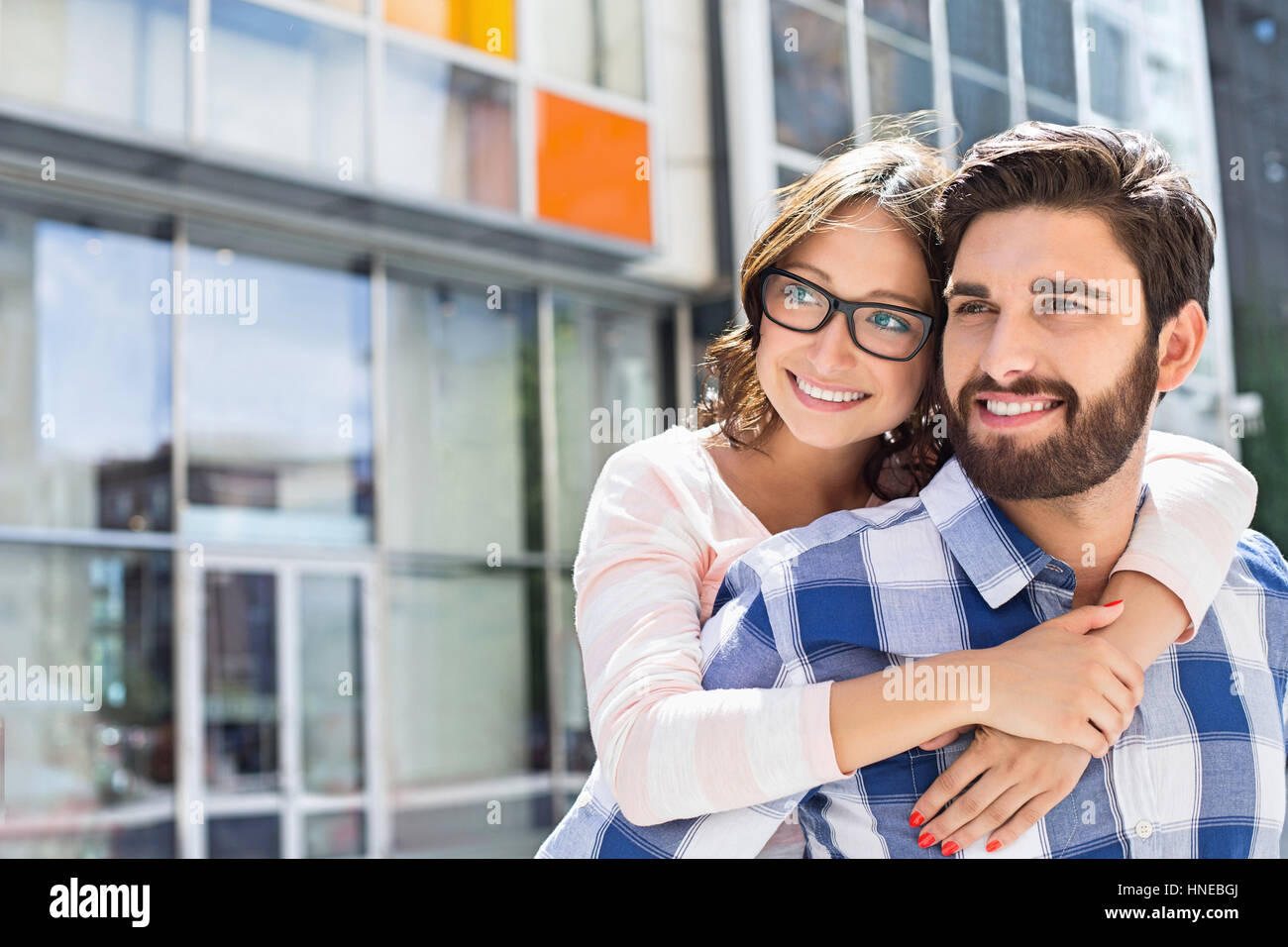 Loving Man piggybacking woman in city Photo Stock