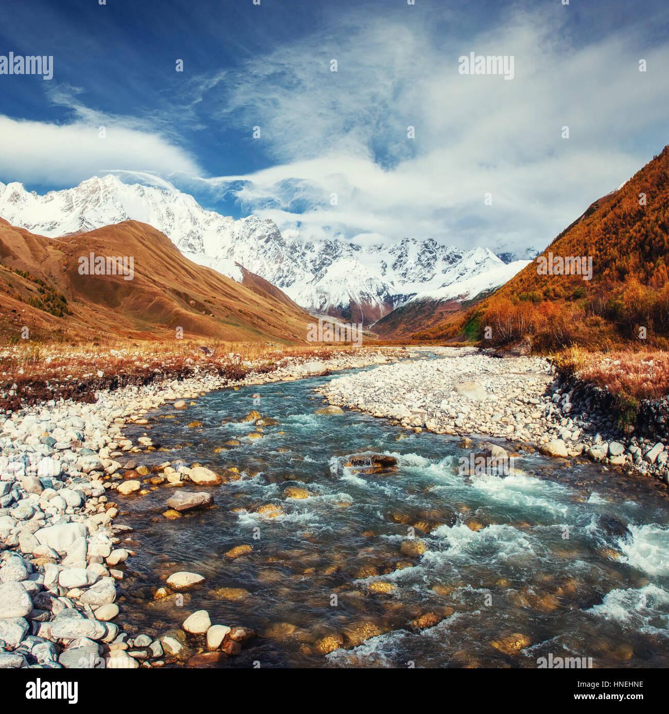 Les montagnes enneigées et la rivière de montagne bruyante Photo Stock