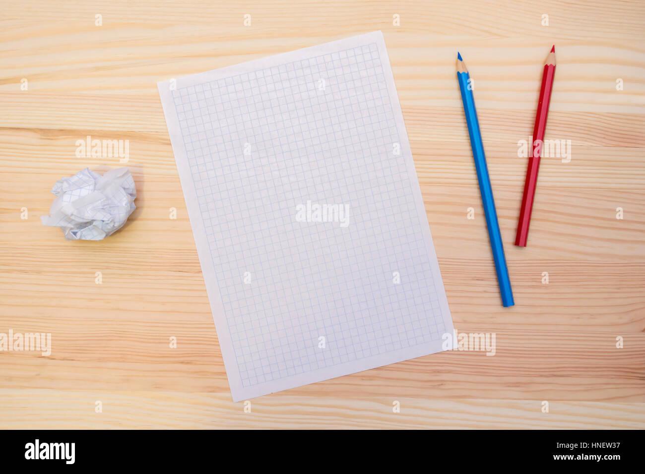 une feuille de papier et crayons sur la table en bois
