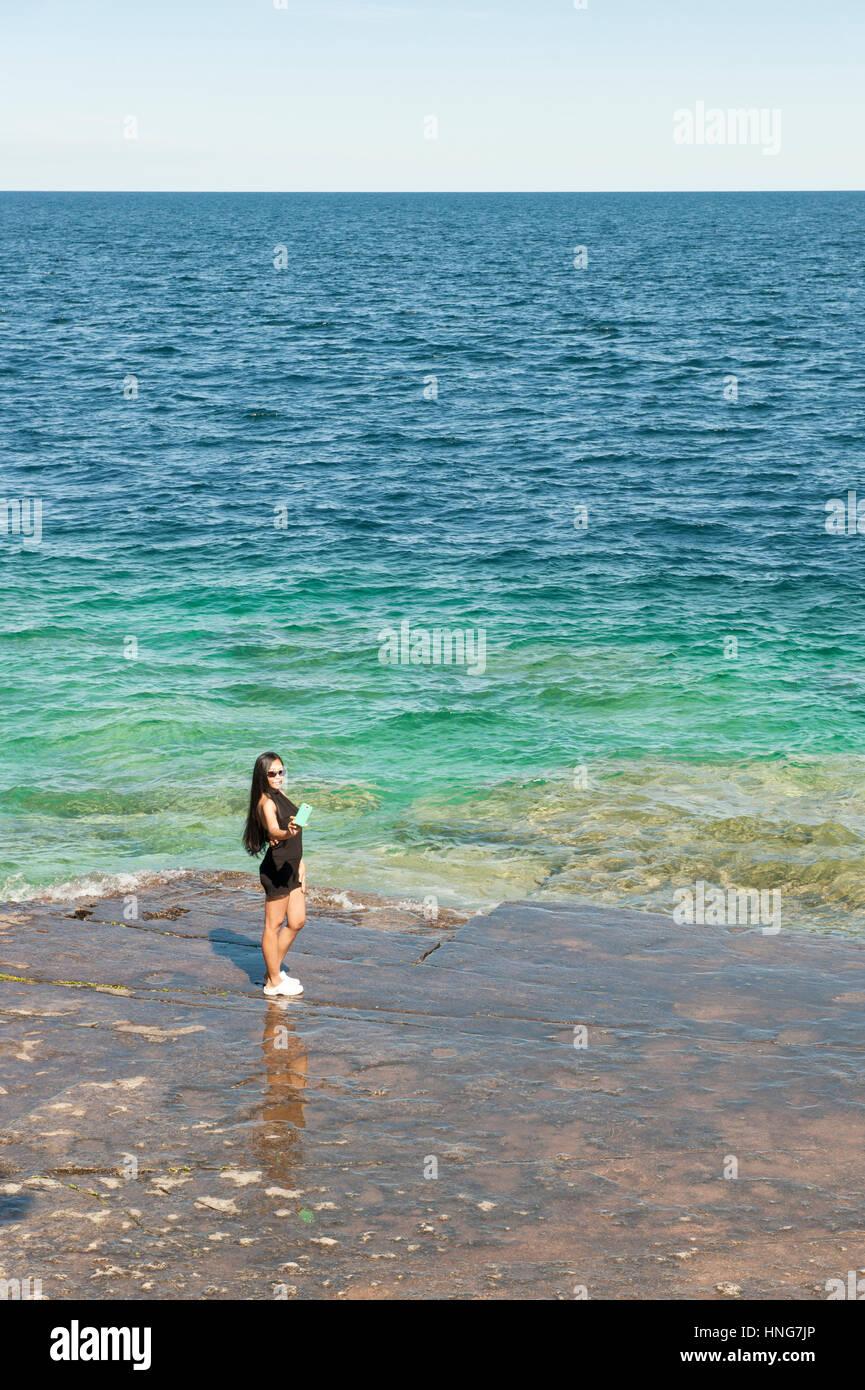 Prendre un touriste asiatique femelle avec un smartphone selfies par le bord du lac Huron, de la baie Georgienne, Photo Stock