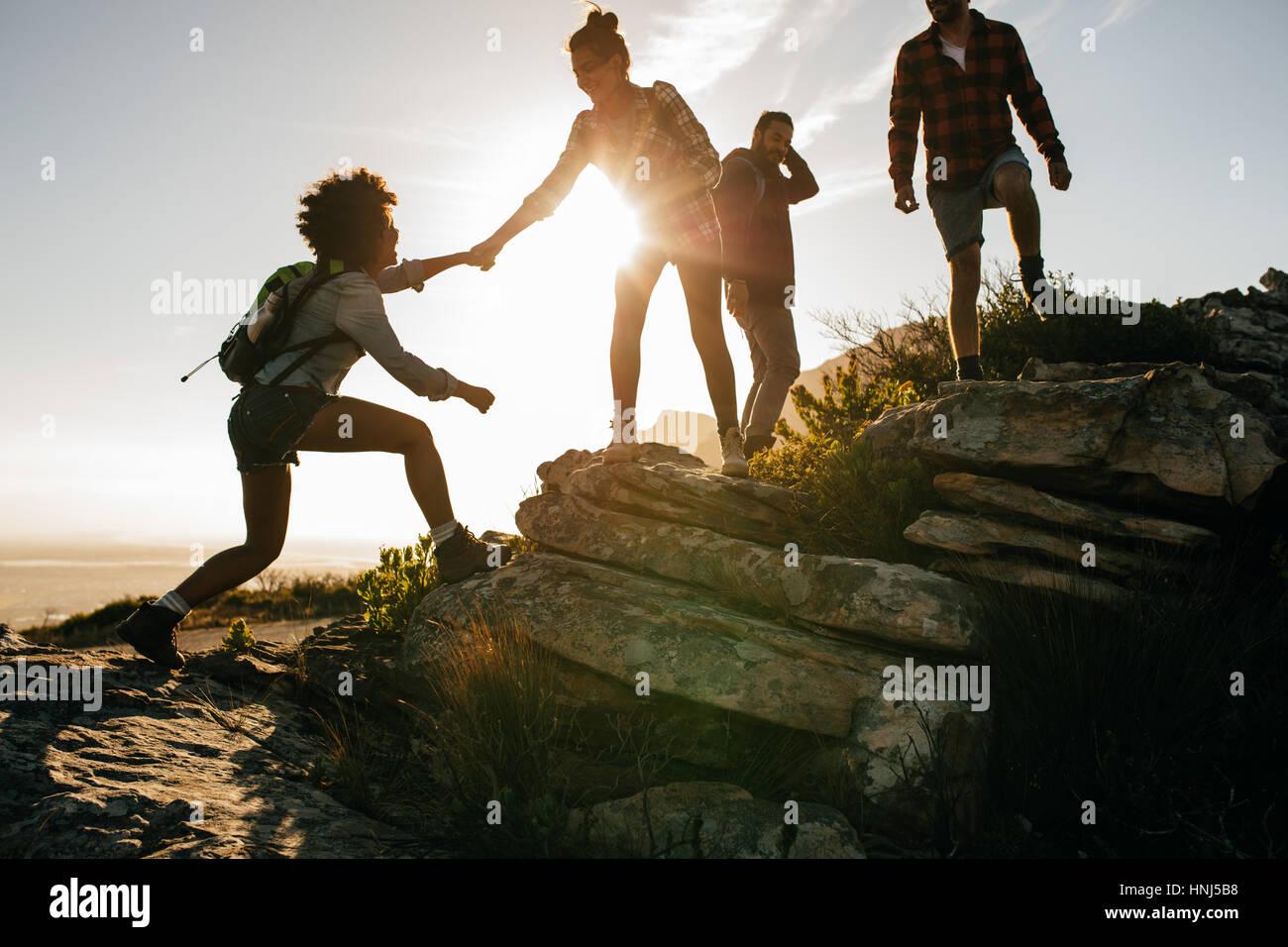 Groupe de randonneurs sur une montagne. Femme d'aider son amie à escalader un rocher. Les jeunes en montagne Photo Stock