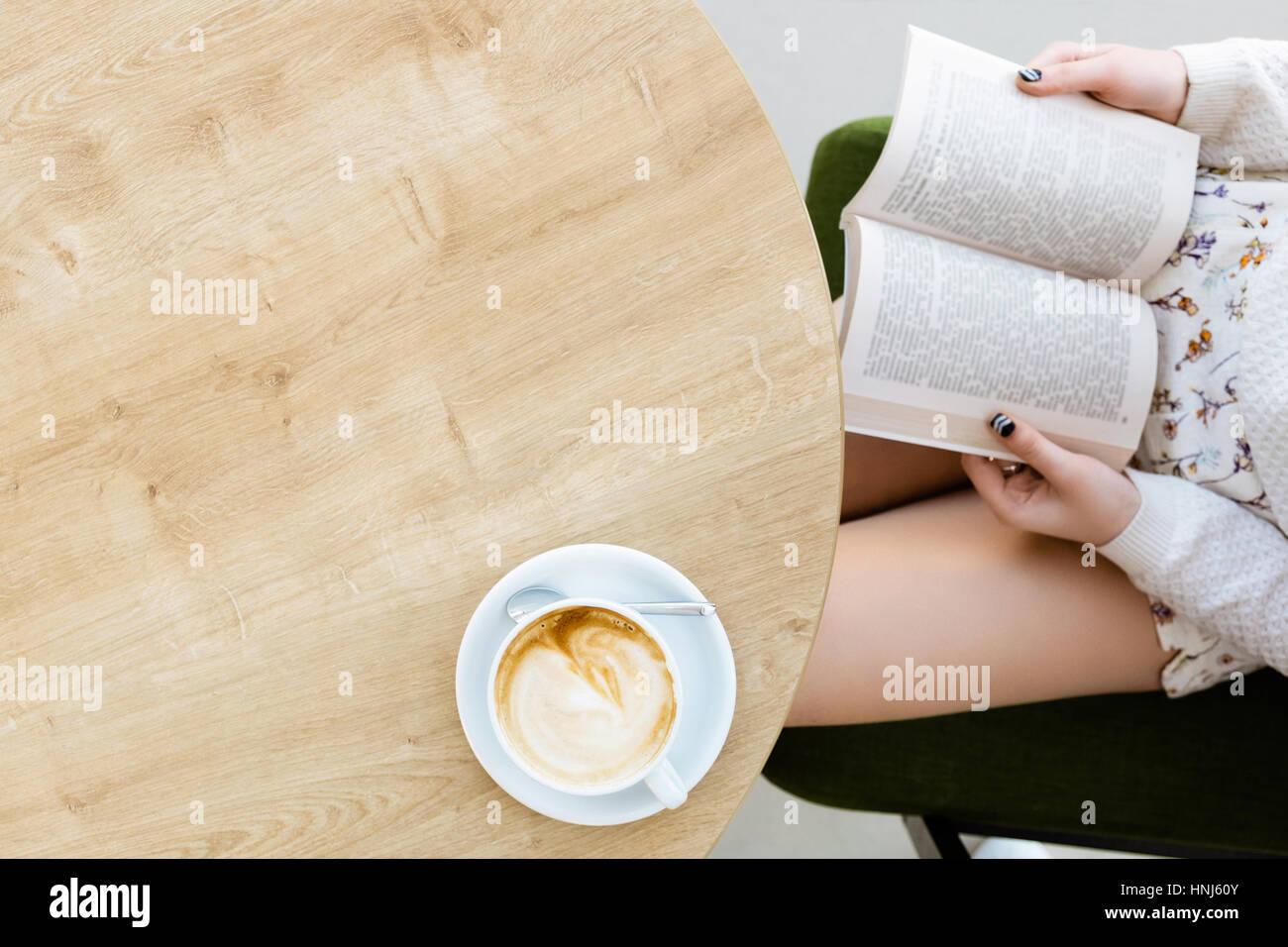 Les jambes de la jeune fille, livre, tasse de café sur la table Photo Stock