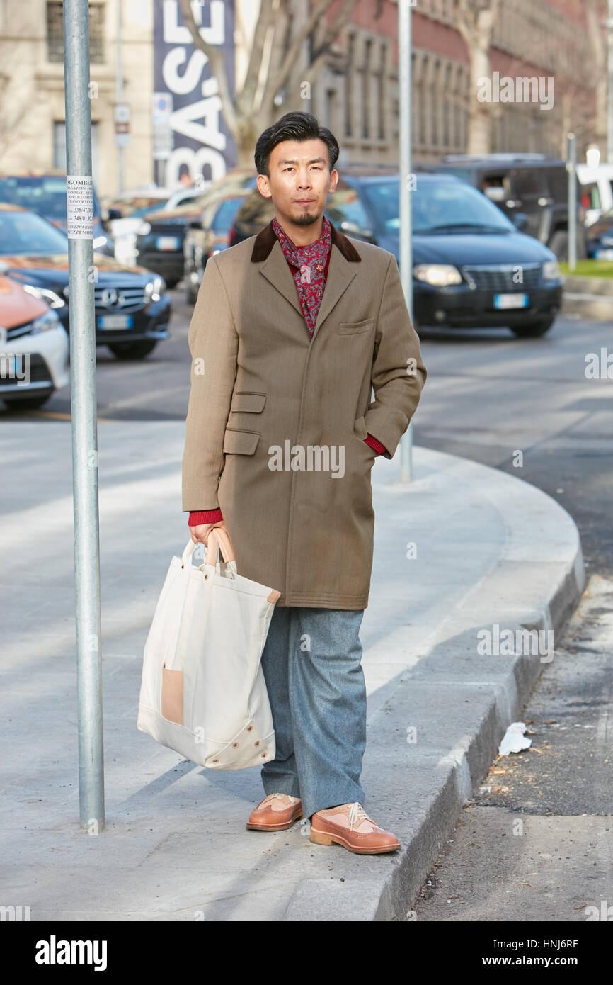 Homme élégant avec brown manteau et foulard rouge avant d'Emporio Armani fashion show, Milan Fashion Photo Stock