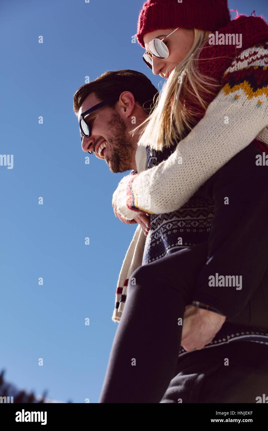 Couple jouent dans la neige. Man giving woman piggyback ride sur les vacances d'hiver. Photo Stock