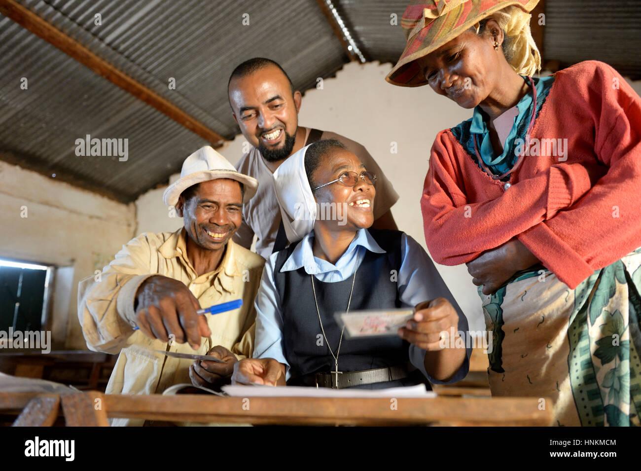 Les villageois de remplir les demandes d'attestation de leur terre sur la place du village, village, commune Photo Stock