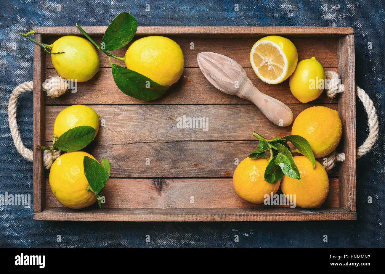 Citrons fraîchement cueillis avec des feuilles dans un coffret en bois sur bleu foncé, fond contreplaqué Photo Stock