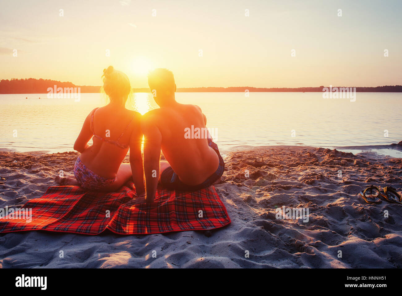 Couple romantique sur la plage au coucher de soleil colorés Photo Stock