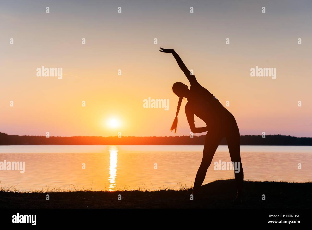Fille au coucher du soleil par le lac Photo Stock
