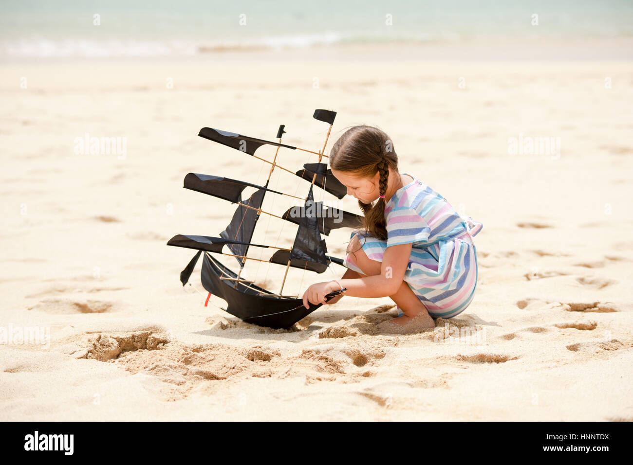 Cute little girl playing on the beach navire volant cerf-volant. Bénéficiant de l'enfant vacances Photo Stock