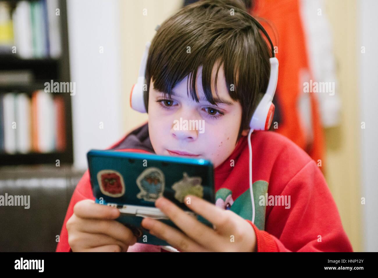 Garçon de 12 ans jouer avec jeu vidéo Photo Stock