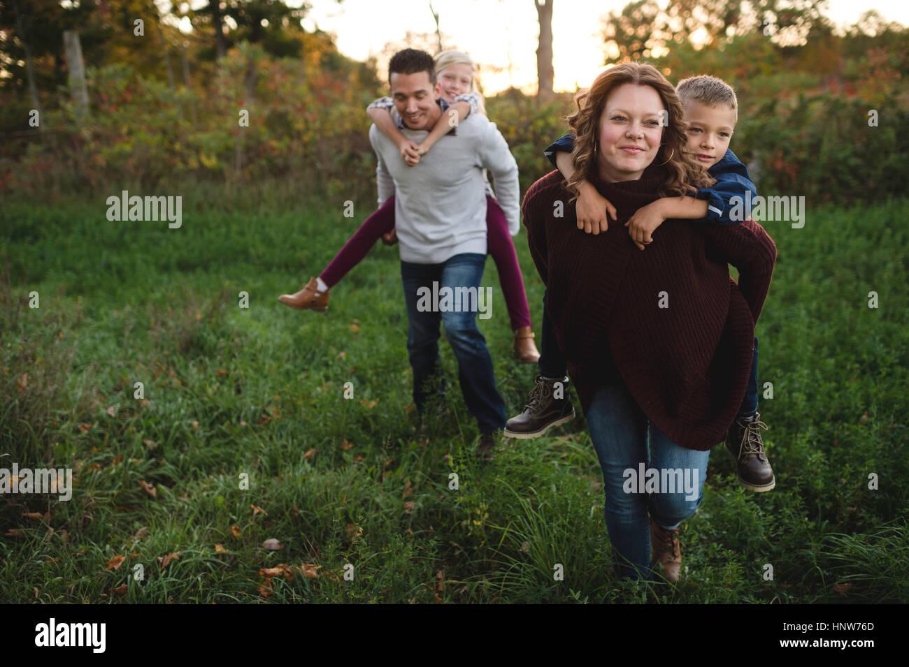 Donner aux enfants les parents piggy back in field Photo Stock