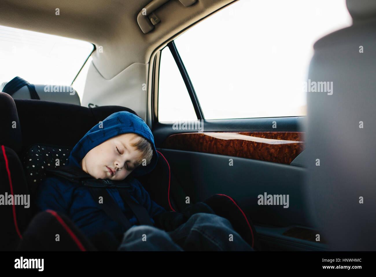 Jeune garçon endormi in back seat of car Photo Stock