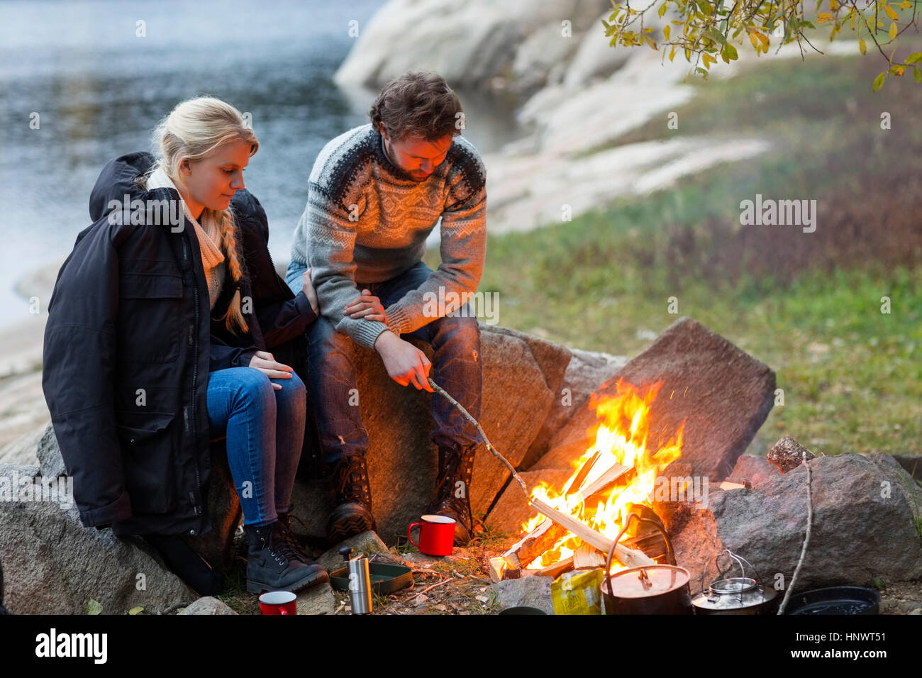 Couple sitting by campfire sur Lakeshore Banque D'Images