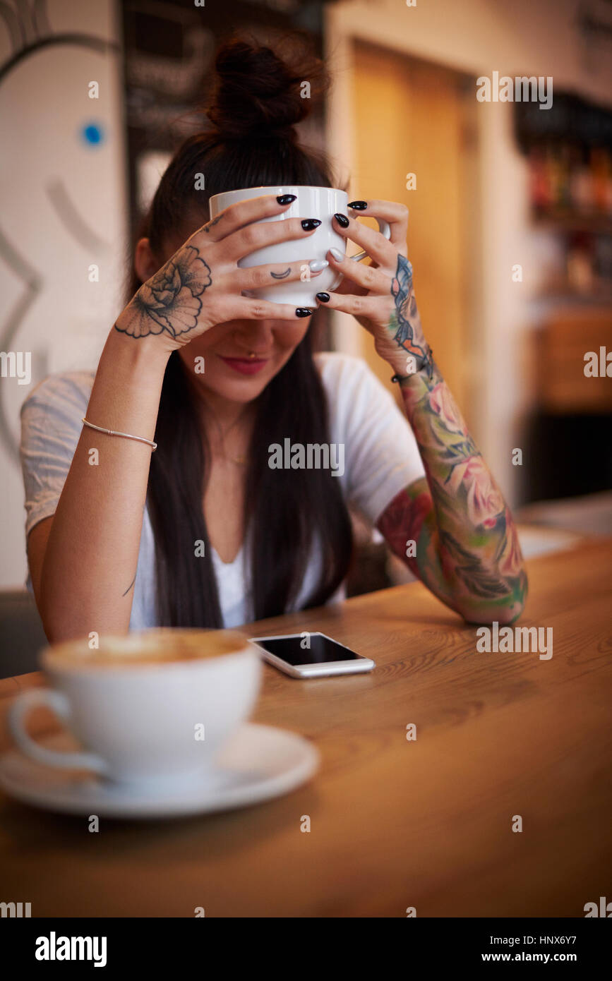 Tattooed Woman holding cup looking down at smartphone Photo Stock