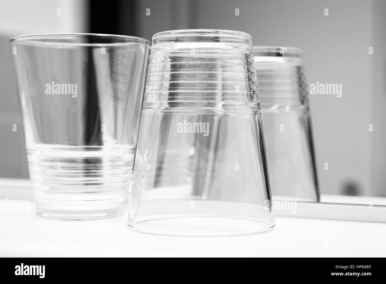 Verres vides se tenir sur la plate-forme blanche près du miroir, noir et blanc photo gros plan Banque D'Images