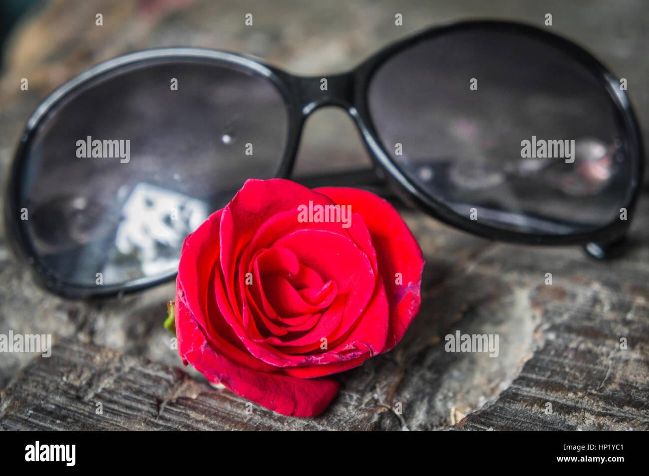Les lunettes de soleil et rose rouge posé sur une table en bois. close- 26c80e51ddc0