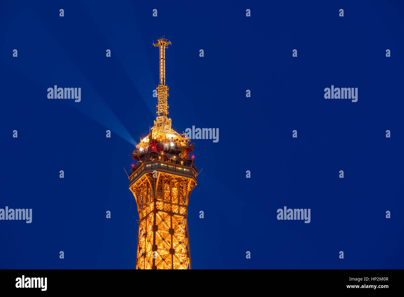 Le haut de la Tour Eiffel illuminée au crépuscule. Champs-de-Mars, 7e arrondissement, Paris, France Photo Stock