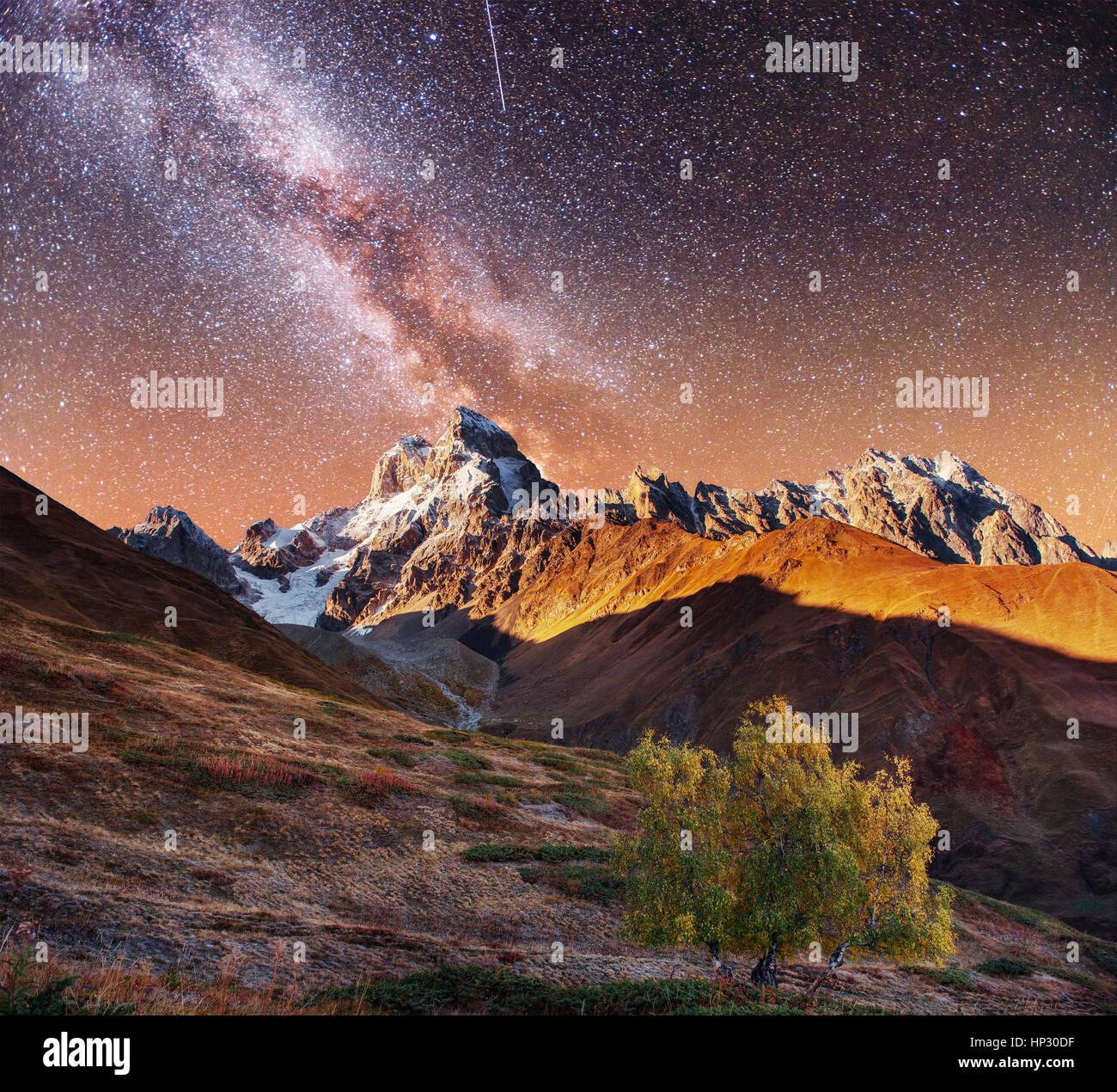 Collage fantastique. Ciel étoilé au-dessus de sommets de montagnes enneigées. Photo Stock