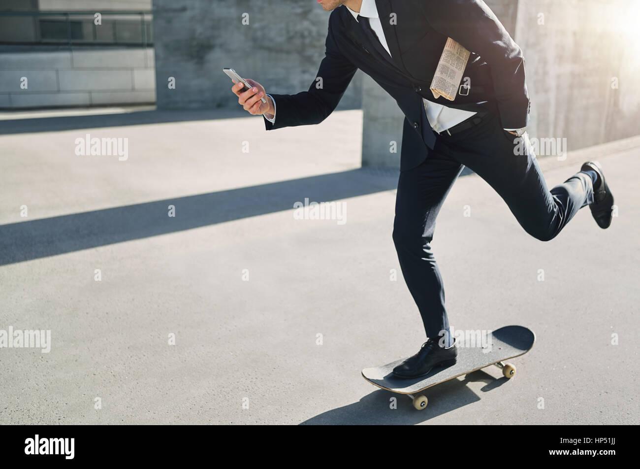 Vue de face d'un homme d'affaires sur un skateboard en regardant son téléphone en déménagement Photo Stock