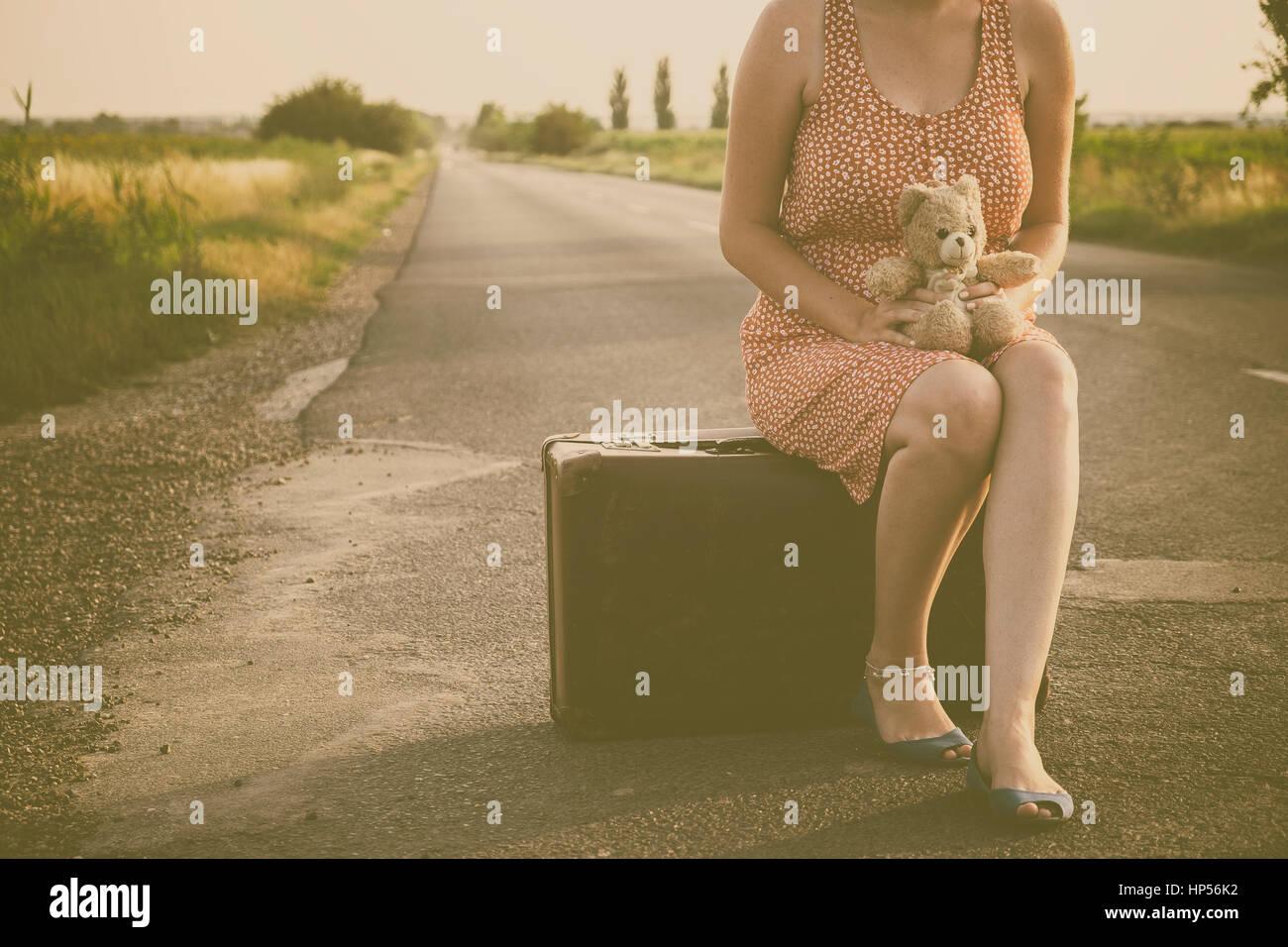 Femme sur la route d'été à coucher du soleil Photo Stock