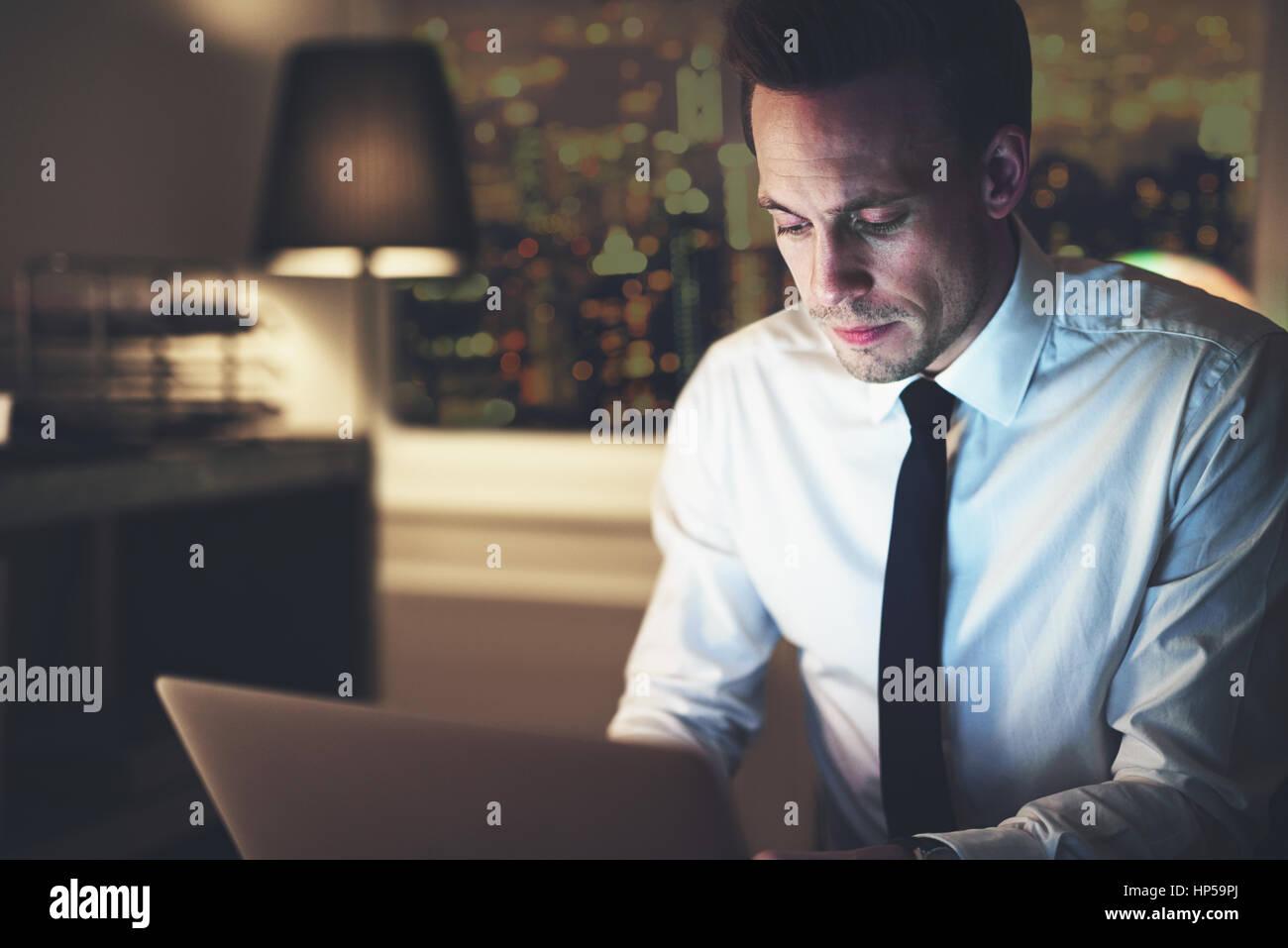 Businessman working on laptop la nuit assis au bureau, grande ville en arrière-plan, Heures supplémentaires Photo Stock