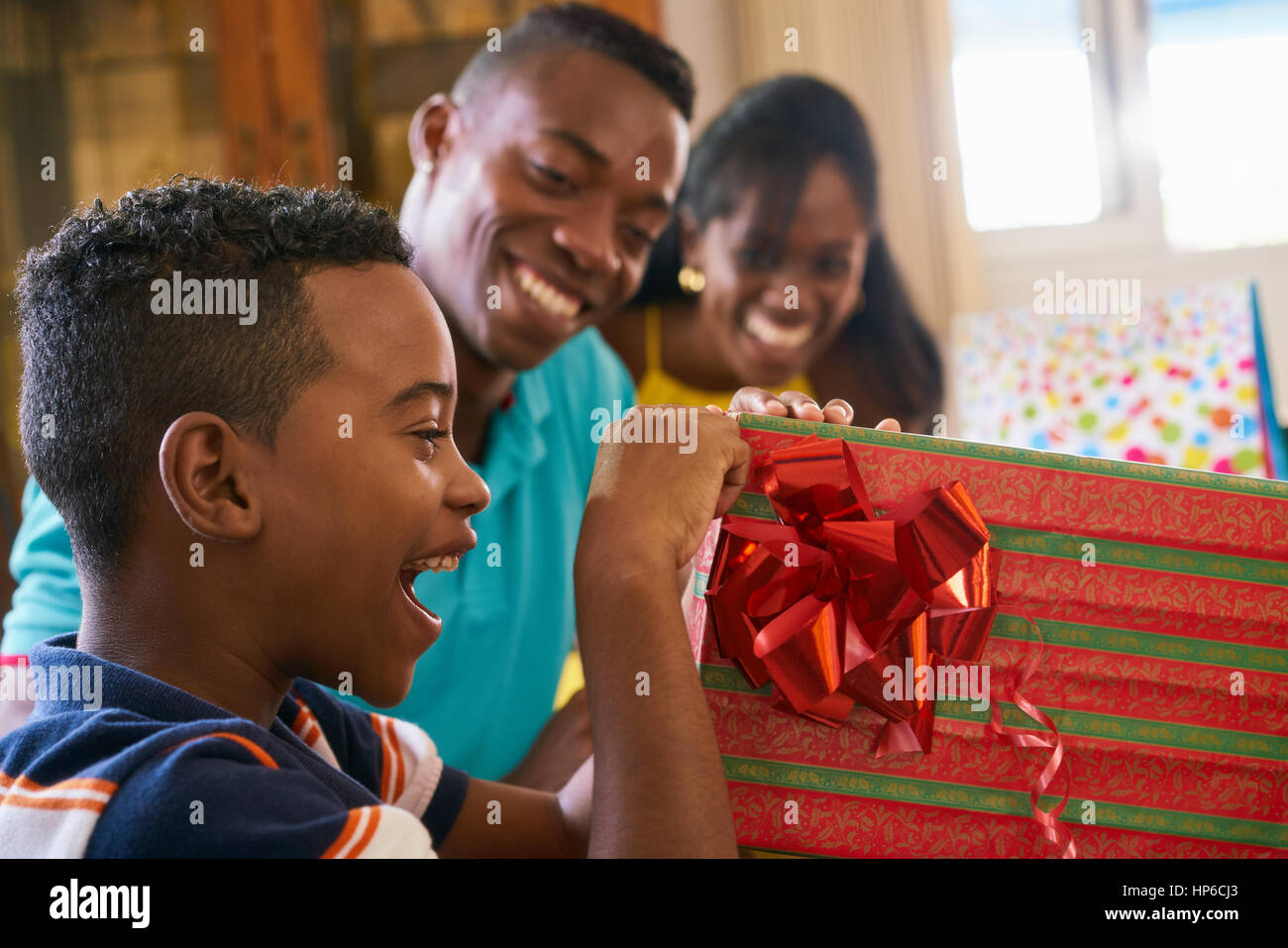 Happy black famille à la maison. African American father, mother and child celebrating birthday, s'amusant Photo Stock