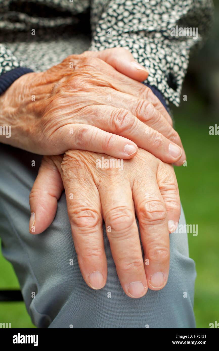 Femme âgée toucher sa main ridée Photo Stock