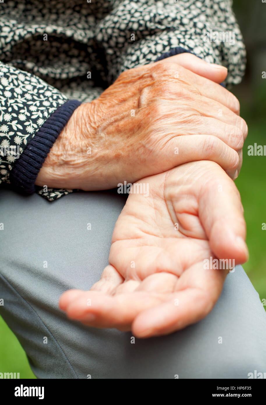 Une vieille femme tenant son poignet douloureux Photo Stock