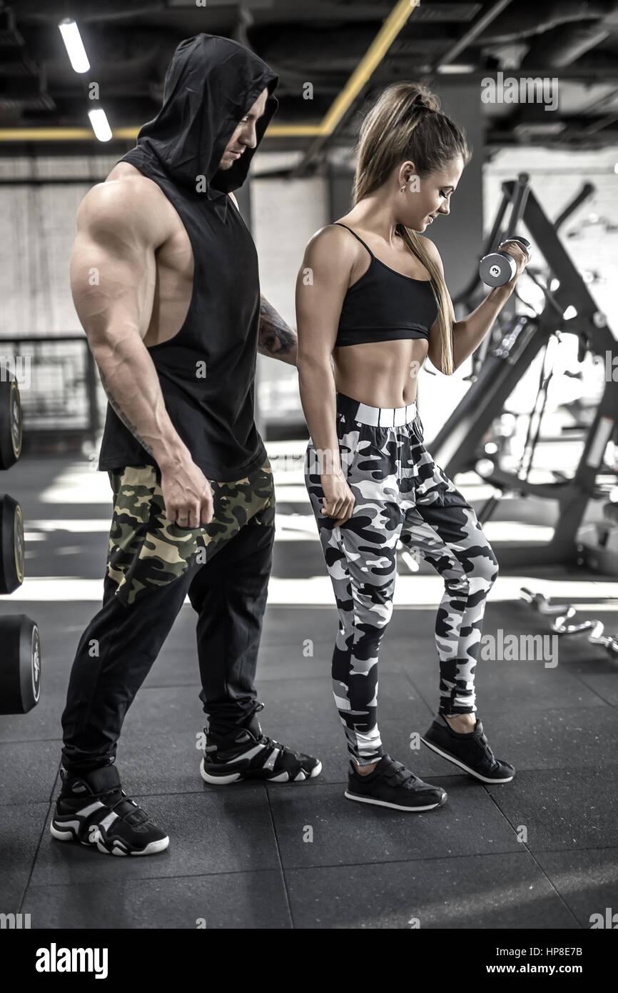Athletic couple dans le sport. Jeune fille fait l exercice avec un haltère  et 6b008fad9ca