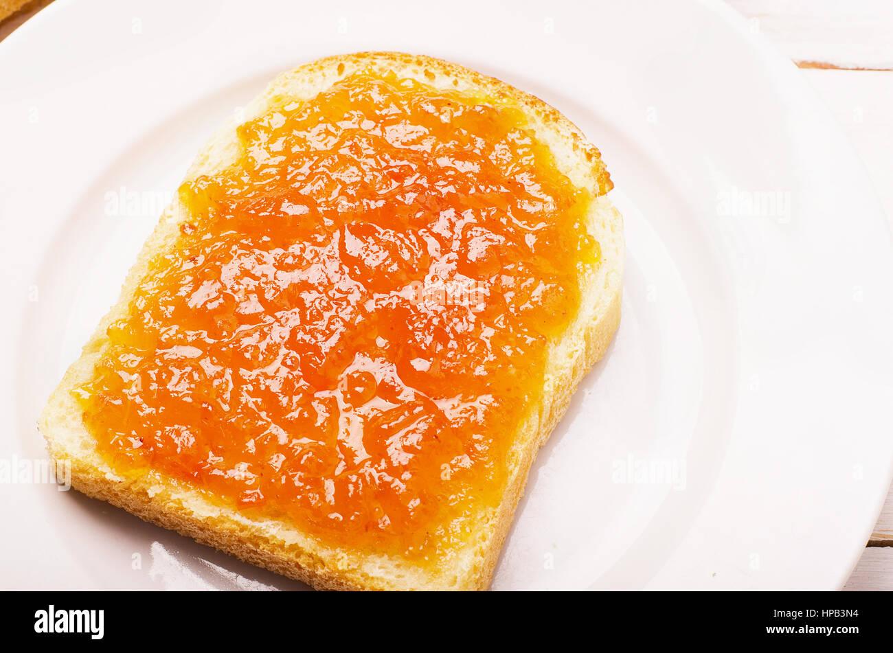 Le pain avec confiture orange pêche dans une assiette sur tableau blanc Photo Stock