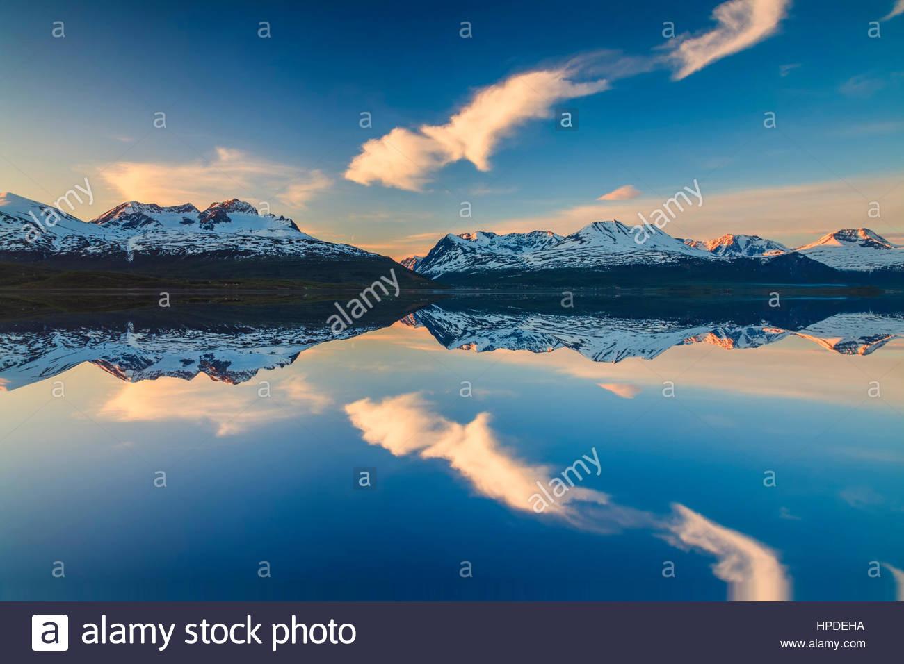 De réflexion de montagnes dans le fjord norvégien au coucher du soleil. Photo Stock