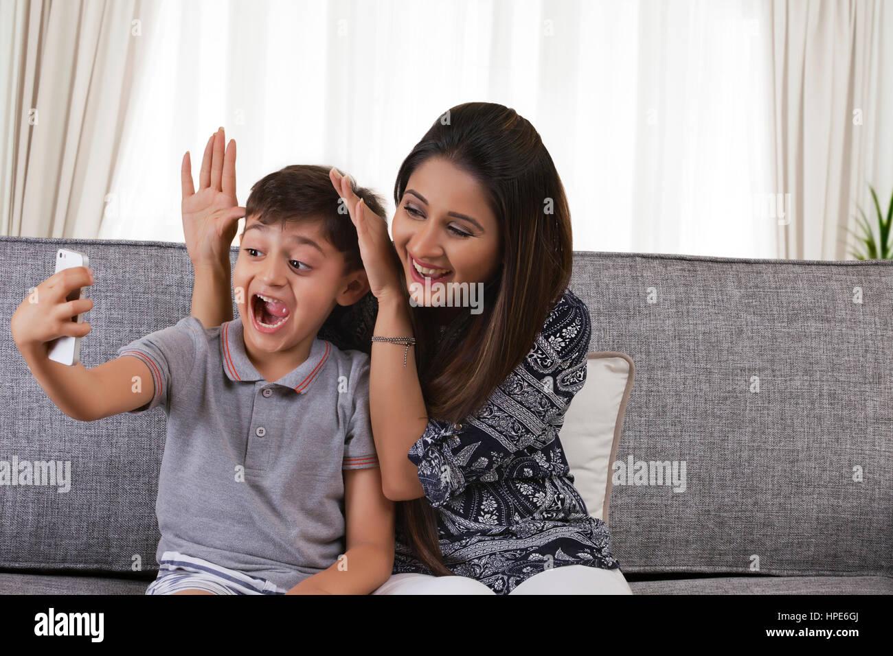 Garçon en tenant des selfies lui-même et faire de geste stupide mère Photo  Stock 3945a3e32f5b