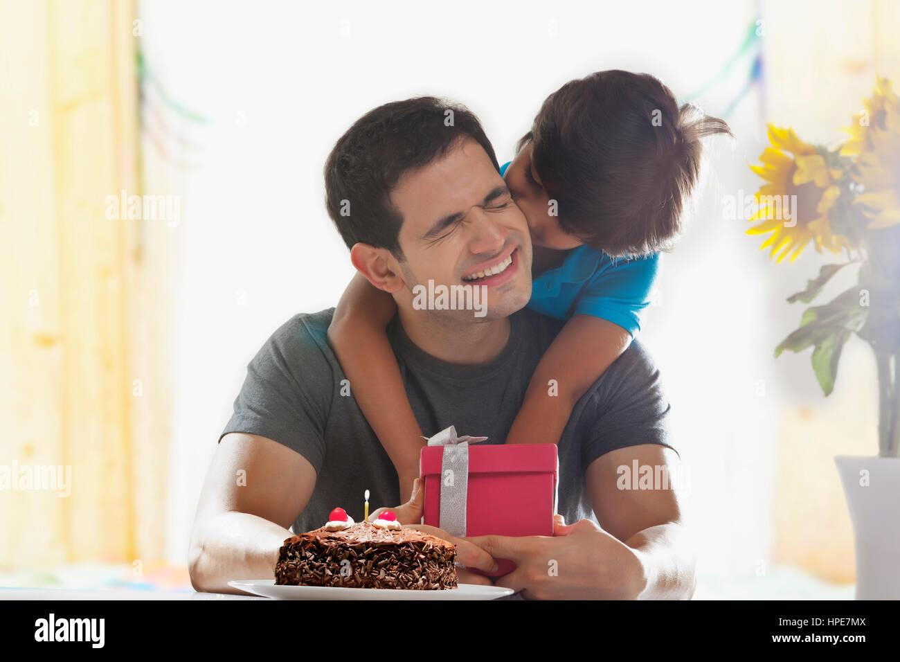 Fils surprenant son père avec le cadeau d'anniversaire Photo Stock