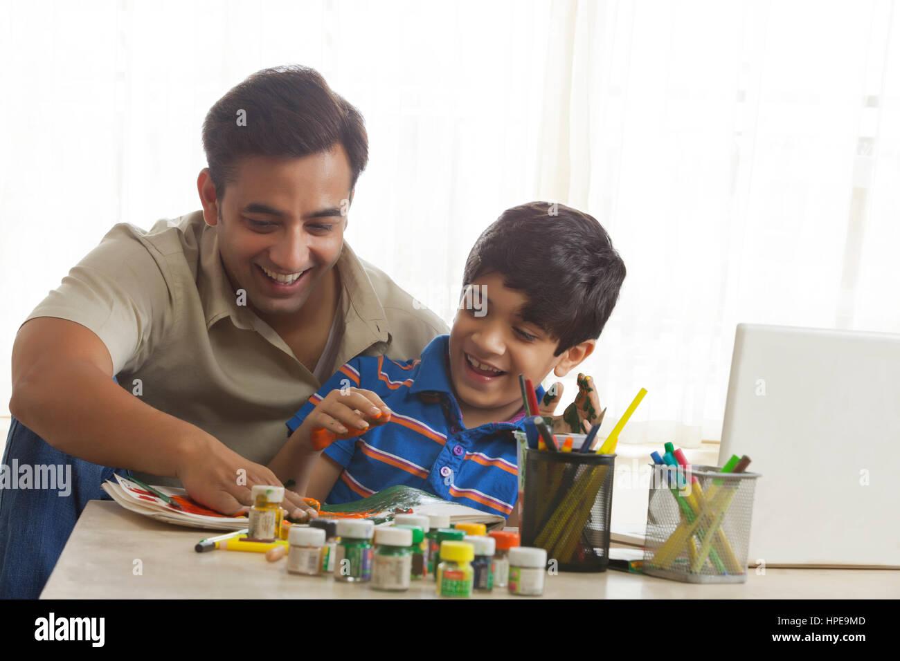 Père et fils la peinture au doigt ensemble Photo Stock