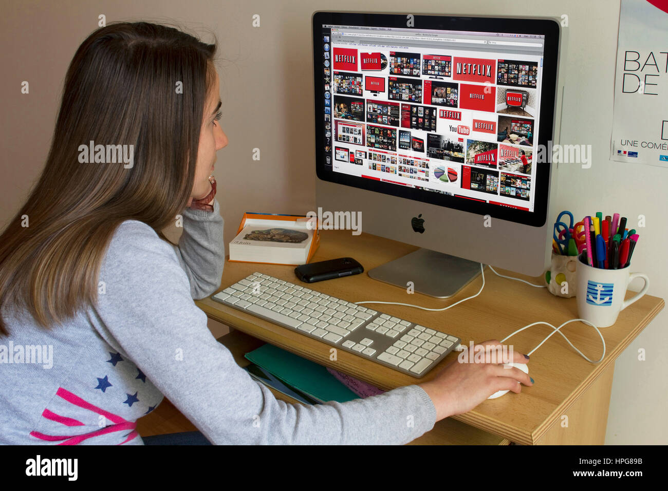 Lycéenne devant un écran d'ordinateur affichant Netflix. Photo Stock