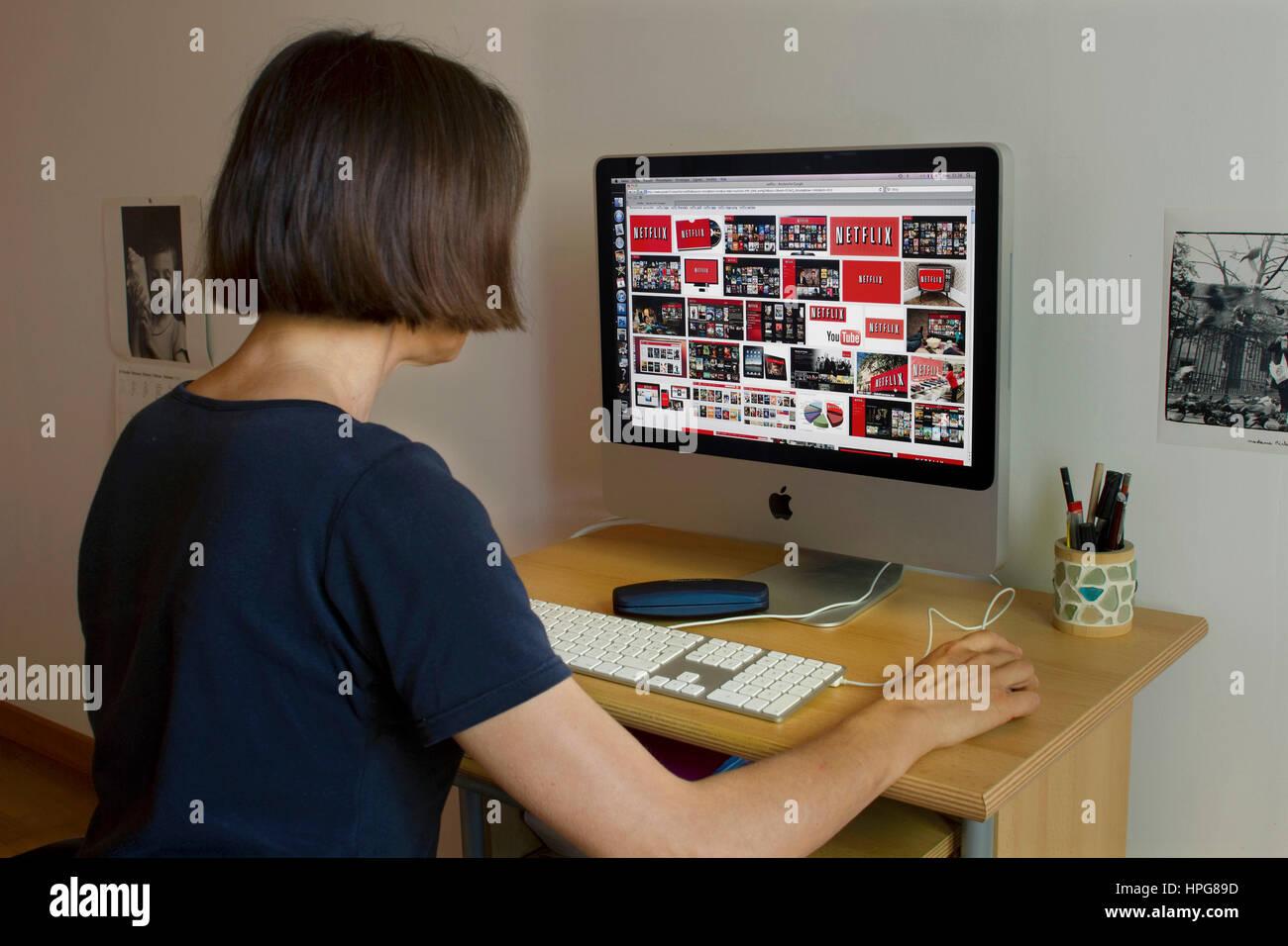 Femme en face d'un écran d'ordinateur affichant Netflix. Photo Stock