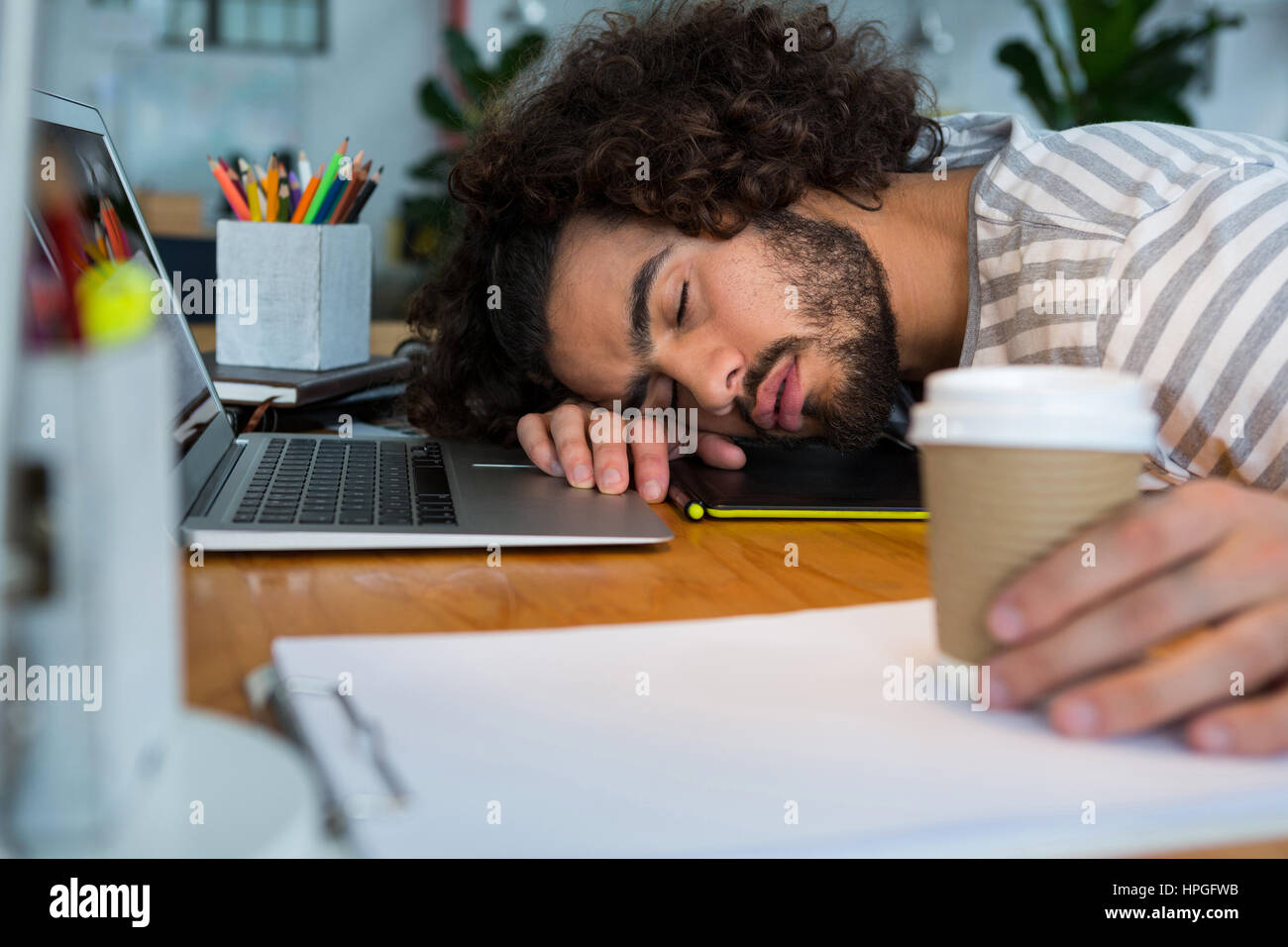 Graphiste surchargés de dormir sur son bureau à la creative office