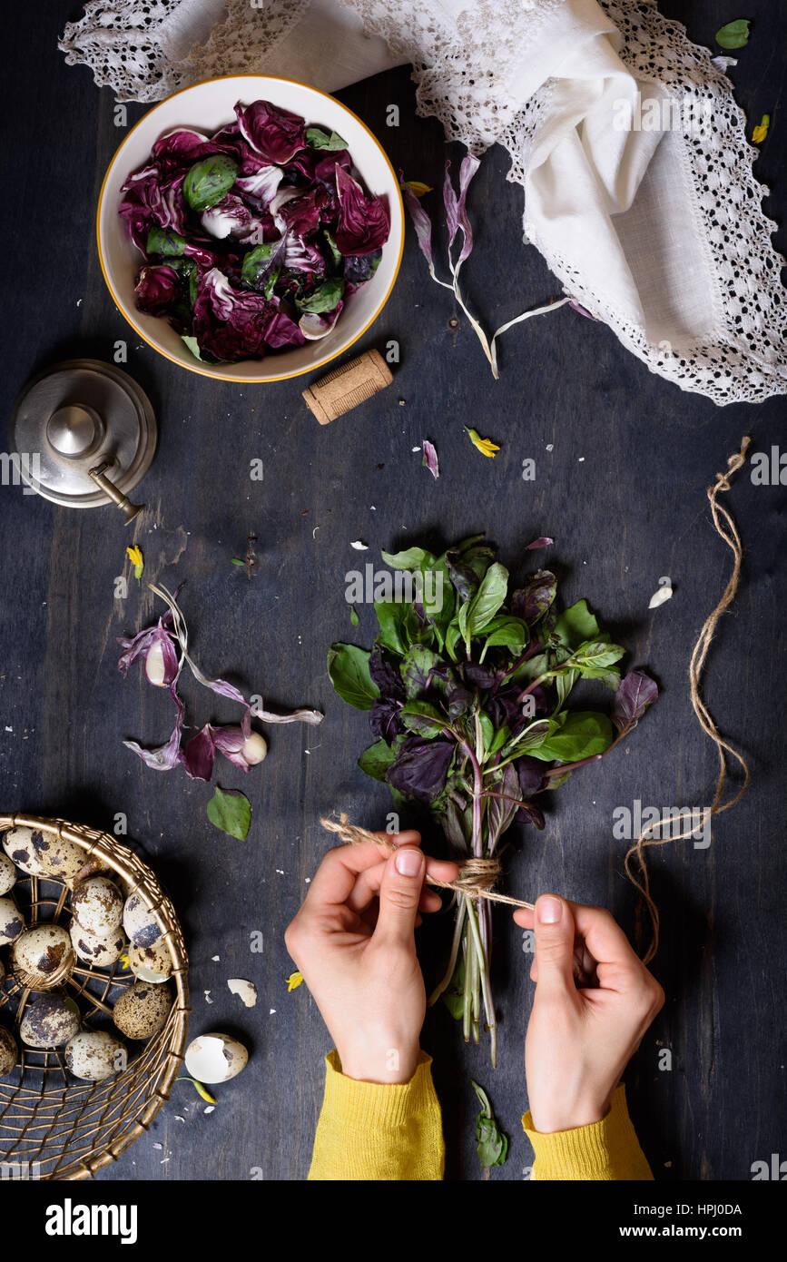 Herbes, réunis en un groupe et attaché, plus de table rustique avec salade et oeufs de ferme. Vue de dessus. Photo Stock