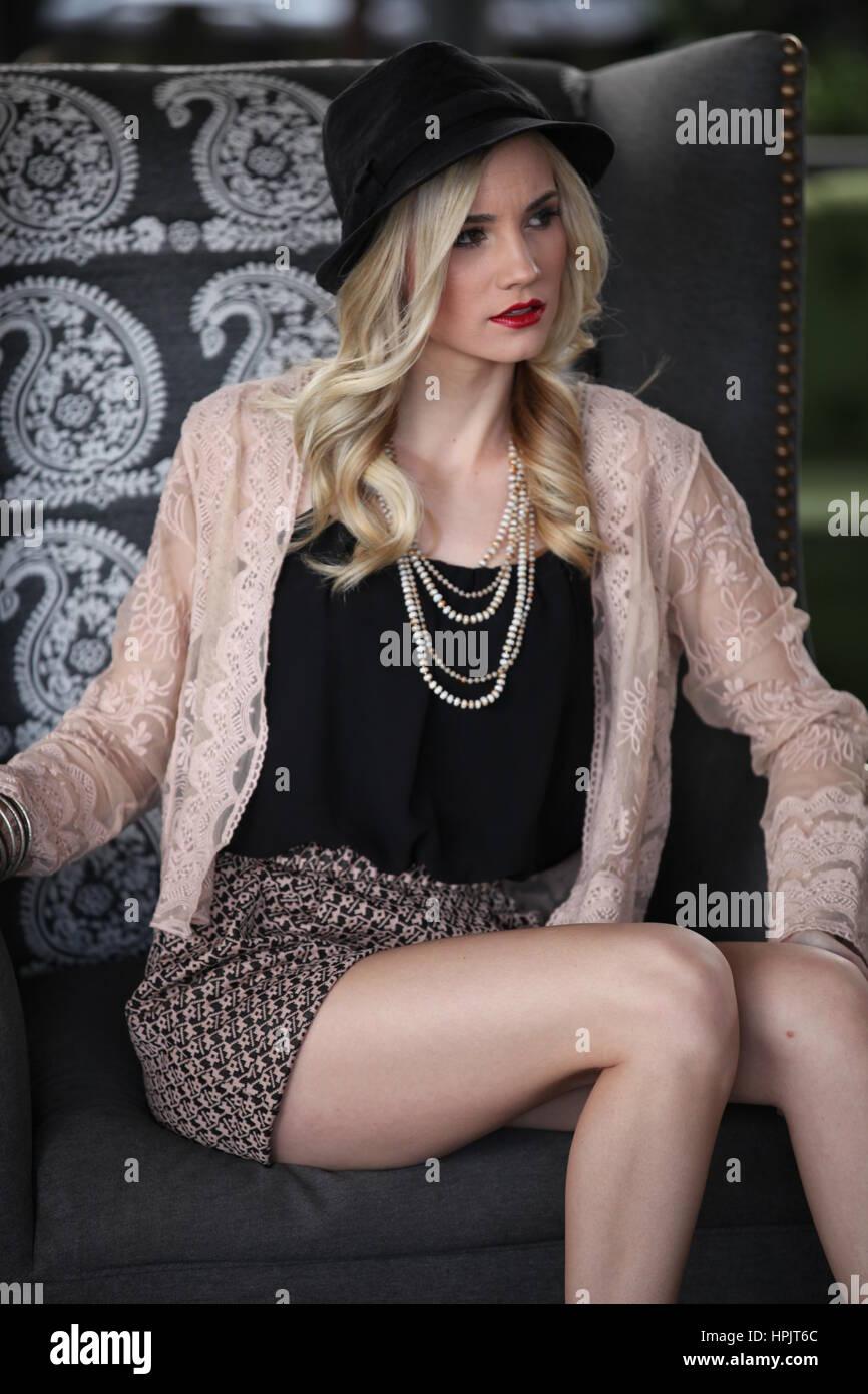 Cute girl sophistiqués se détend en chaise haute Photo Stock